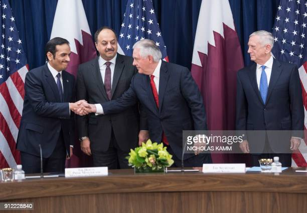 US Secretary of State Rex Tillerson shakes hands with Qatari Foreign Minister Sheikh Mohammed bin Abdulraham alThani as Defense Minister Khaled bin...