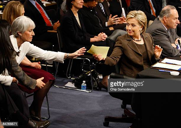 Secretary of Statedesignate and US Senator Hillary Clinton passes a note to aids while testifying during her confirmation hearing before the Senate...