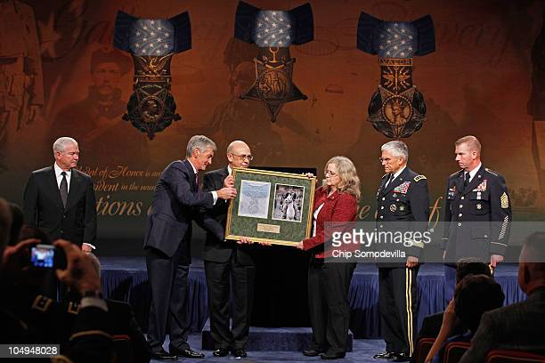 S Secretary of the Army John McHugh hands a framed certificate and photo to Philip and Maureen Miller the parents of Medal of Honor recipient US Army...