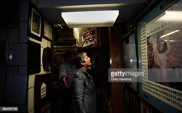 Secretary of the Department of Homeland Security Janet Napolitano looks over memorial pictures from the 9/11 terrorist attacks at a firehouse July...