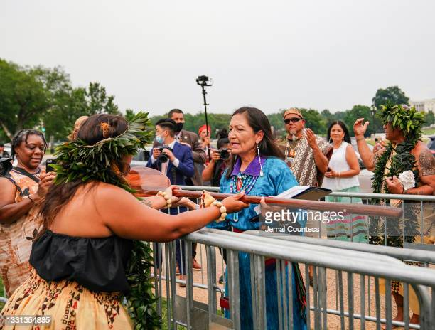 Secretary of the Interior Deb Haaland accepts a gift of a traditional Hawaiian Canoe paddle carved by James Hedani from a member of the Indigenous...