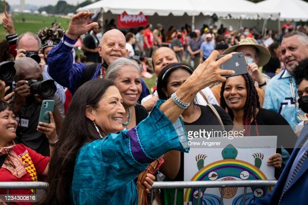 Secretary of the Interior Deb Haaland takes a photo with guests after speaking during a welcome ceremony for a totem pole carved by the House of...