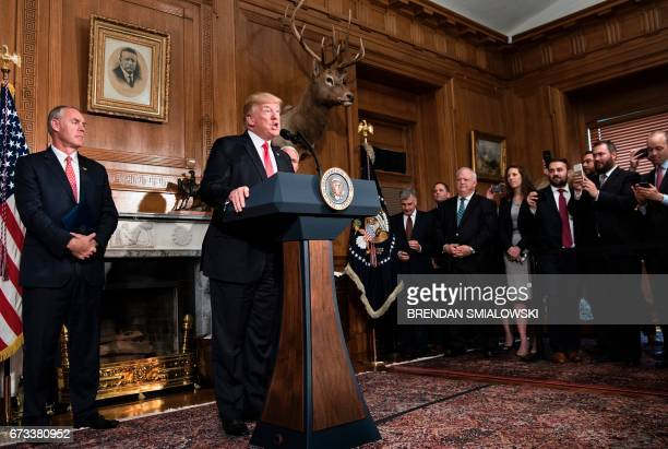 US Secretary of the Interior Ryan Zinke listens while US President Donald Trump speaks before signing an executive order to review the Antiquities...