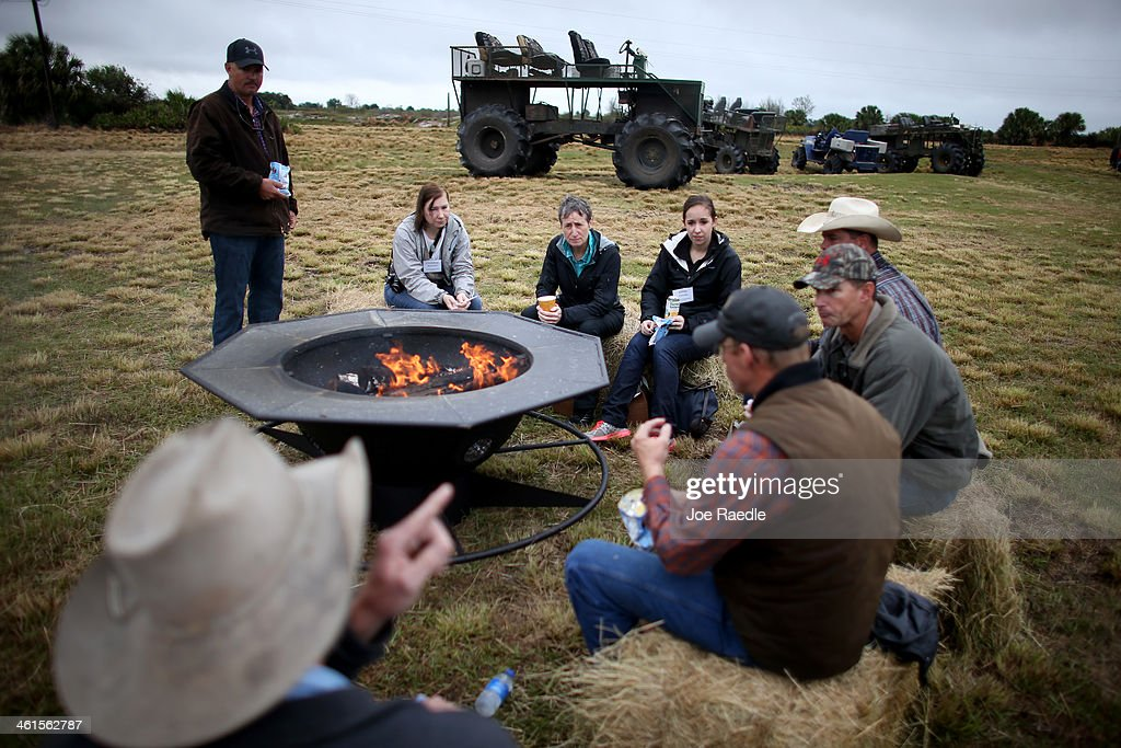 Secretary of the Interior Sally Jewell (3rd L) sits around a fire during a visit to meet with ranchers and private landowners on January 9, 2014 in Okeechobee, Florida. Jewell made a visit to the area to discuss the next steps for the Everglades Headwaters National Wildlife Refuge and Conservation Area.