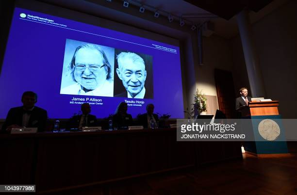 Secretary of the Nobel Committee for Physiology or Medicine Thomas Perlmann stands next to a screen displaying James P Allison and Tasuku Honju the...