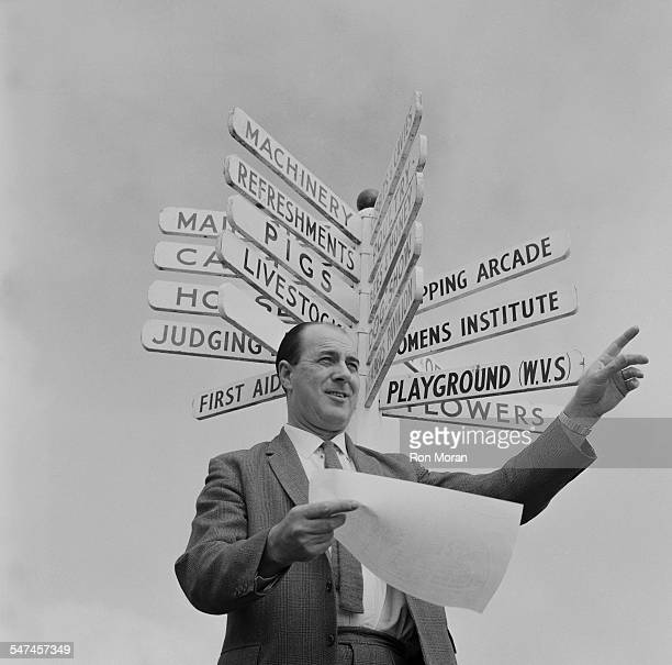 Secretary of the Royal Cornwall Show Albert Riddle stands beneath a sign showing events taking place at the agricultural show circa June 1967