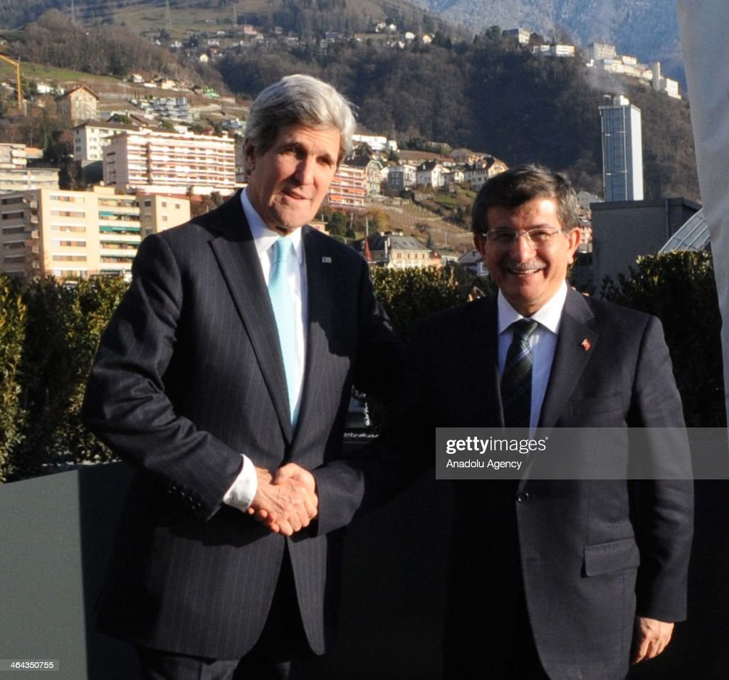 US Secretary of the State John Kerry (L) shakes hand with Turkish Foreign Minister Ahmet Davutoglu (R) on the first day of Geneva-II peace talks in Montreux, Switzerland, on January 22, 2014.