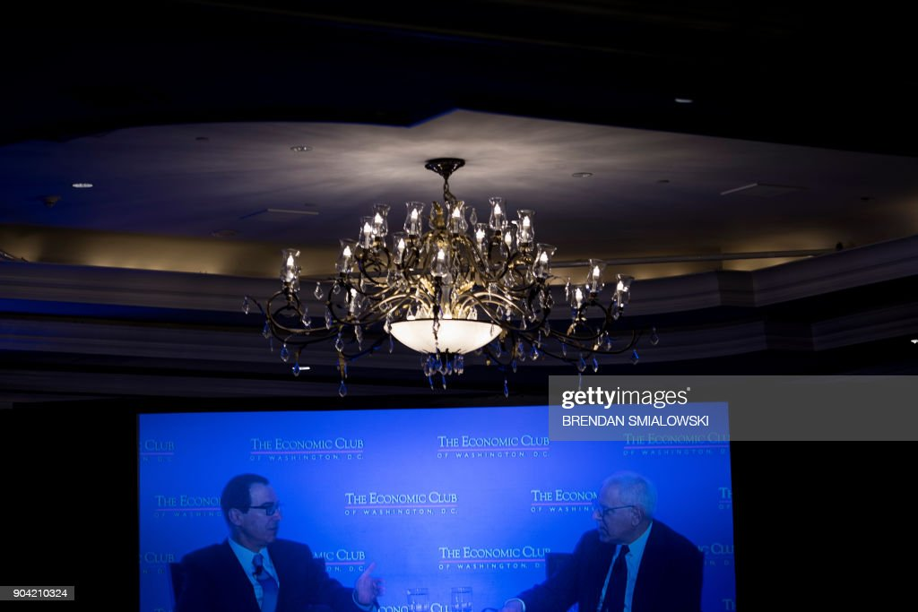 US Secretary of the Treasury Steven Mnuchin (L) is seen on a screen speaking with David Rubenstein during a meeting at the Economics Club of Washington on January 12, 2018 in Washington, DC. / AFP PHOTO / Brendan Smialowski