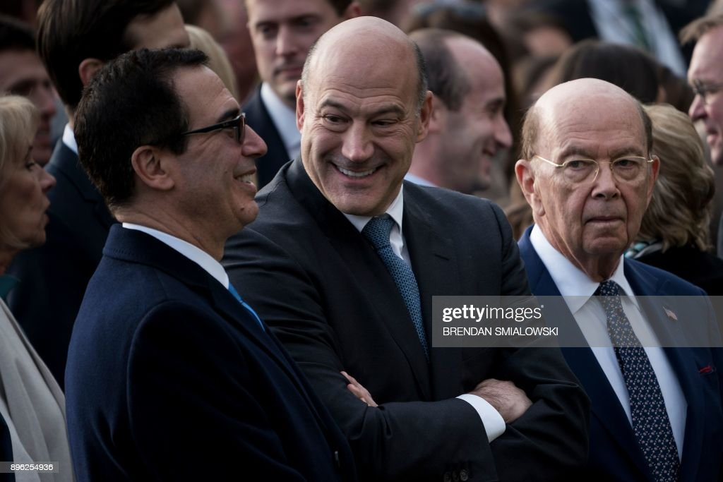 US Secretary of the Treasury Steven Mnuchin (L), National Economic Council Director Gary Cohn (C) and US Secretary of Commerce Wilbur Ross wait for US President Donald Trump to speak about newly passed tax reform legislation during an event at the White House December 20, 2017 in Washington, DC. Trump hailed a 'historic' victory Wednesday as the US Congress passed a massive Republican tax cut plan, handing the president his first major legislative achievement since taking office nearly a year ago. / AFP PHOTO / Brendan Smialowski