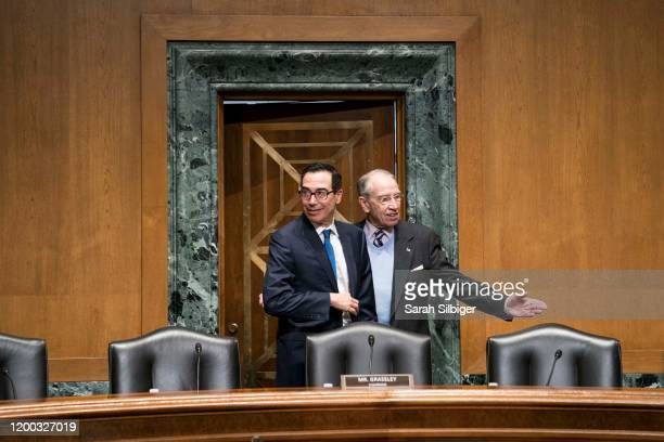 Secretary of the Treasury Steven Mnuchin speaks to Senator Chuck Grassley as he arrives to testify before the Senate Finance Committee during a...