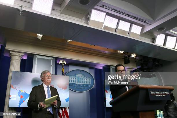 Secretary of the Treasury Steven Mnuchin takes questions as National Security Advisor John Bolton looks on during a press briefing at the White House...
