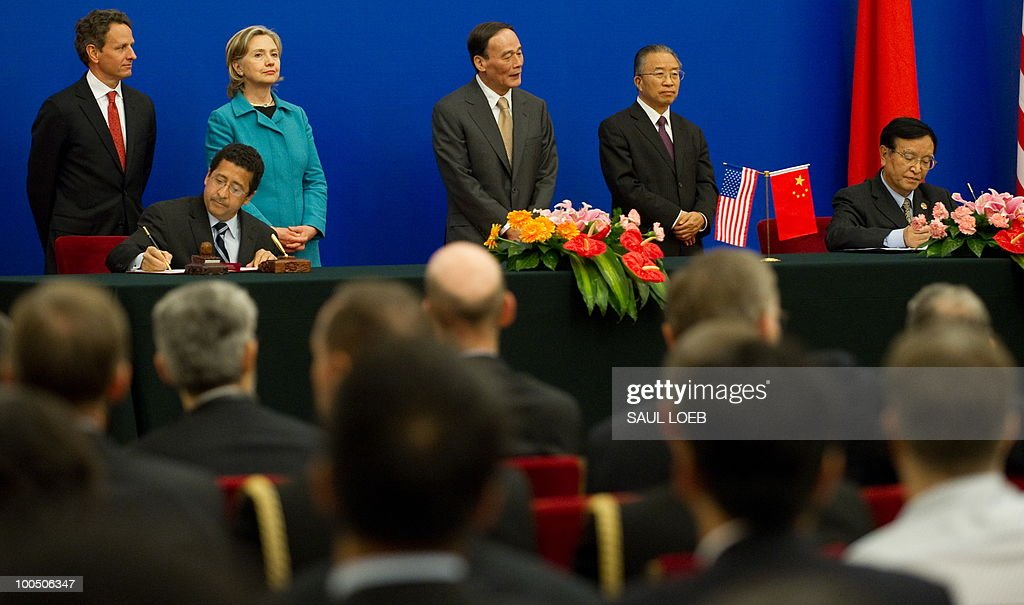 US Secretary of Treasury Timothy Geithner (L), US Secretary of State Hillary Clinton (2nd L), Chinese Vice-Premier Wang Qishan (2nd R) and Chinese State Councilor Dai Bingguo (R) watch as a US official and his Chinese counterpart sign a Memorandum of Understanding during a signing ceremony at the conclusion of the Second Round of the US-China Strategic & Economic Dialogue in Beijing, May 25, 2010. US Secretary of State Hillary Clinton said two days of high-level Sino-US talks had been 'very productive' but admitted differences remained, especially on economic and trade issues. AFP PHOTO / POOL / Saul LOEB