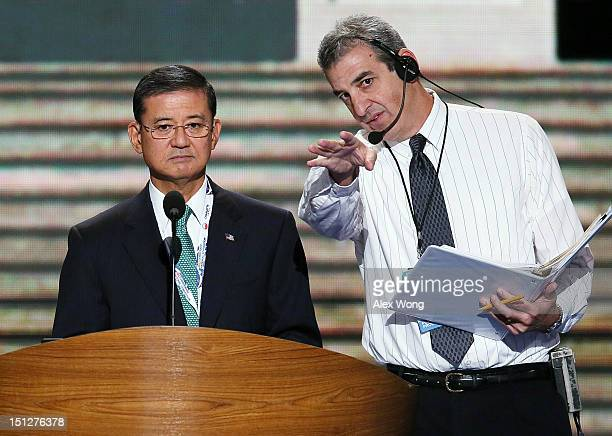 S Secretary of Veterans Affairs Eric Shinseki stands at the podium with stage manager David Cove during a walkthrough on day two of the Democratic...