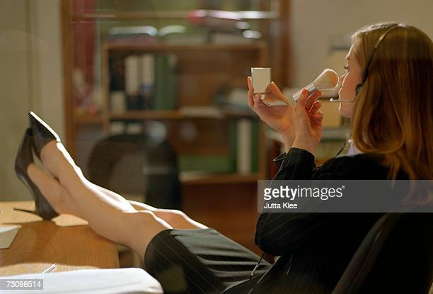 Secretary sitting with her feet up on desk and powdering her nose