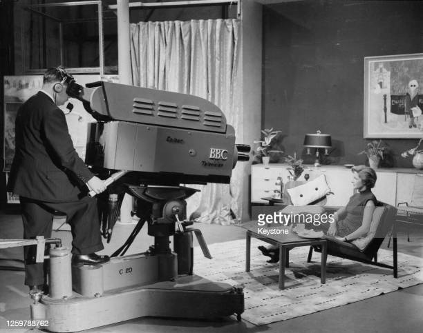 Secretary to the Head of the Television Section Designs Department Ann Veronica Matthews sits on a chair as she is filmed by a colour television...