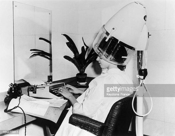 A secretary typing on her typing machine under a hairdryer in a hairsalon designed for such matters in England on December 7 1959 Beside her is also...