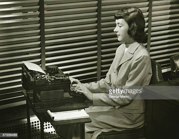 secretary typing on typewriter in office, (b&w) - secretary stock photos and pictures