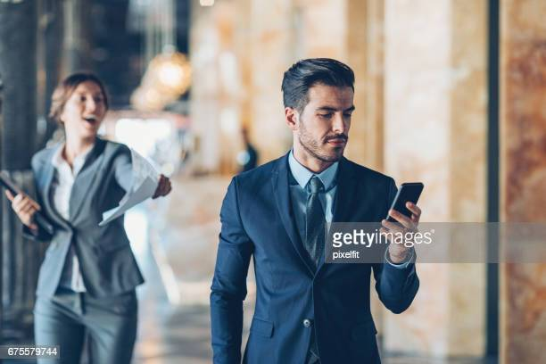 Secretary with documents running after CEO
