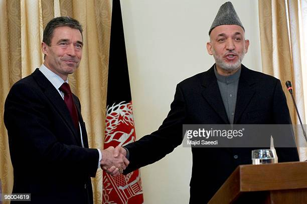 Secretary-General Anders Fogh Rasmussen and Afghanistan's President Hamid Karzai shake hands during a news conference at the Presidential palace on...