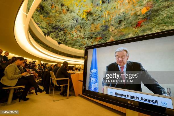 UN SecretaryGeneral Antonio Guterres is seen on a TV screen while addressing the United Nations Human Rights Council on February 27 2017 in Geneva...