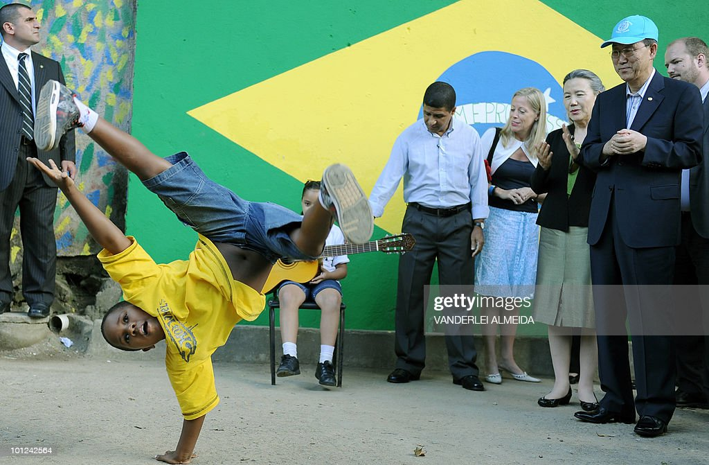 UN Secretary-General Ban Ki-moon (R-blue cap) watches a child dancing during a visit to the Babilonia shantytown in Rio de Janeiro, Brazil, May 27, 2010. Moon is in Brazil to take part in the III Alliance of Civilizations Forum.