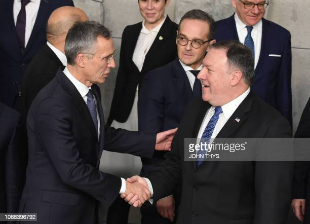 SecretaryGeneral Jens Stoltenberg shakes hands with US Secretary of State Mike Pompeo after posing for a family picture during a foreign minister...