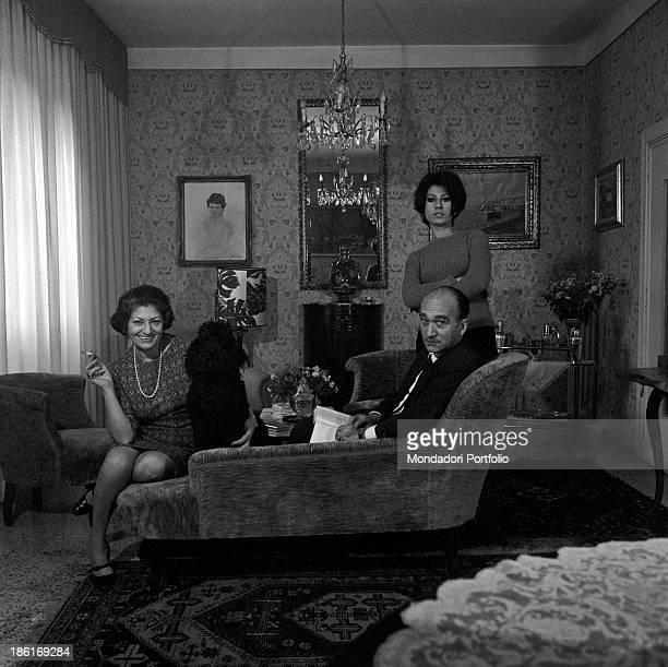 Secretarygeneral of Italian Social Movement Giorgio Almirante his wife Assunta Almirante and their daughter Giuliana de' Medici posing in a living...