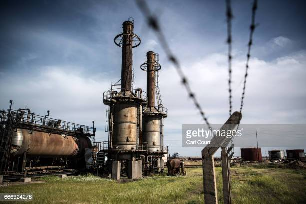 A section of barbed wire fence runs past part of an oil refinery destroyed by retreating Islamic State fighters at the beginning of the Mosul...