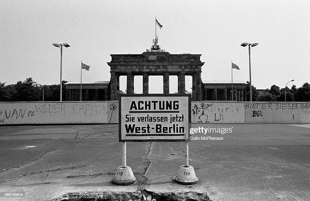 A section of the Berlin Wall at the Brandenburg Gate, seen from the western side of the divide. The Berlin Wall was a barrier constructed by the German Democratic Republic (GDR, East Germany) starting on 13 August 1961, that completely cut off West Berlin from surrounding East Germany and from East Berlin. The Wall was opened on 9. November 1989 allowing free movement of people from east to west.