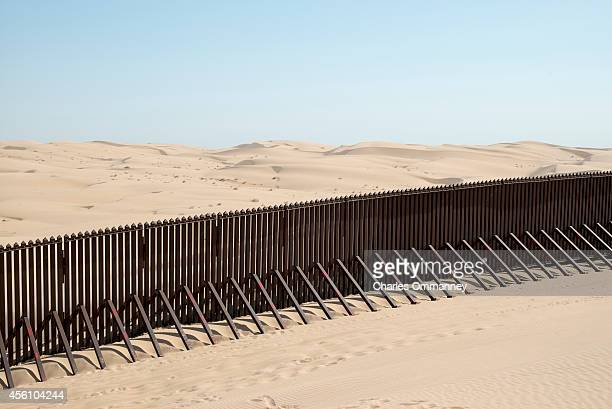 A section of the controversial USMexico border fence expansion project crosses previously pristine desert sands at sunrise on May 24 2014 between...