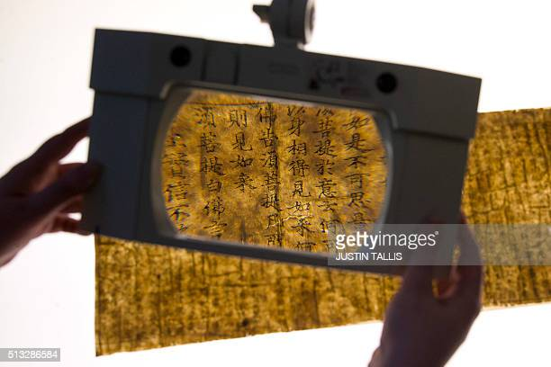 A section of the Diamond Sutra the world's earliest complete dated printed book is seen through a magnifying glass at the British Library in London...