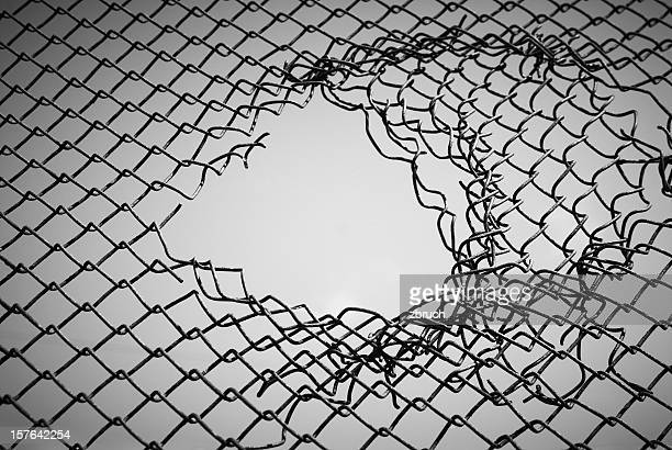 section of wire mesh with a hole in the middle - escapism stock pictures, royalty-free photos & images