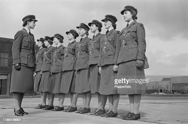 Section Officer Farquahar Petters inspects a line of Women's Auxiliary Air Force recruits in uniform on parade at a Royal Air Force fighter command...