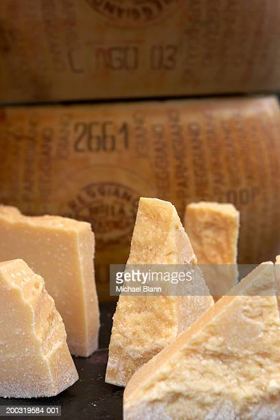 Sections of parmesan cheese on market stall, close-up