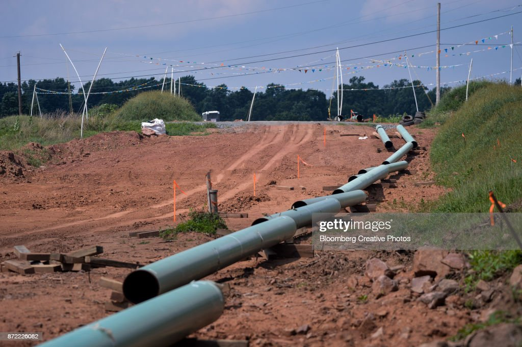 Sections of pipe sit on top of wooden supports at a construction site : Stock Photo