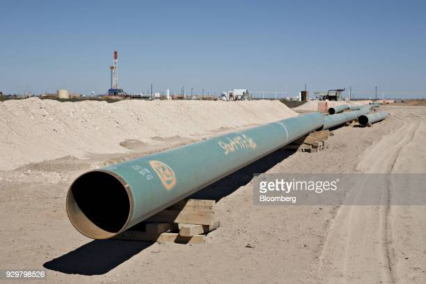 Sections of pipeline lie on the ground near an oil drill rig in the Permian Basin near Pyote Texas US on Friday March 2 2018 Chevron the world's...