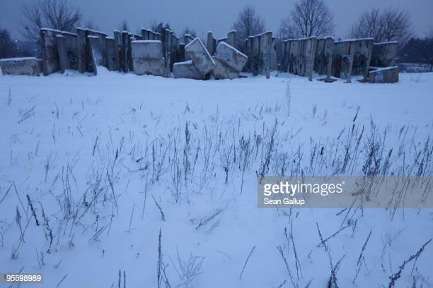 Sections of the former Berlin Wall which once divided East and West Berlin during the Cold War lie covered in snow before dawn just outside Berlin on...