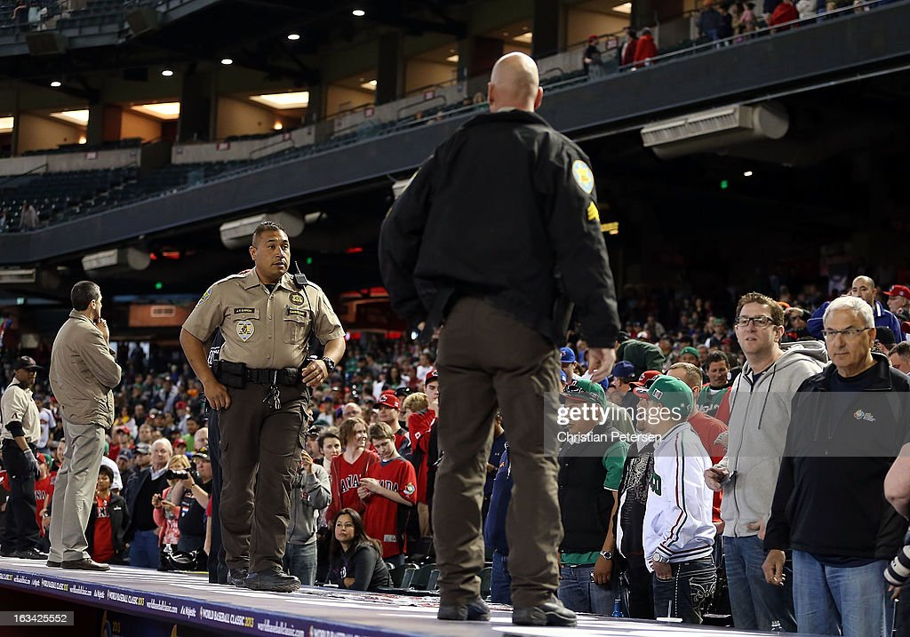 Secuirty and police take postion on top of the dugout after fans threw objects onto the field during the World Baseball Classic First Round Group D game between Mexico and Canada at Chase Field on March 9, 2013 in Phoenix, Arizona. Canada defeated Mexico 10-3.