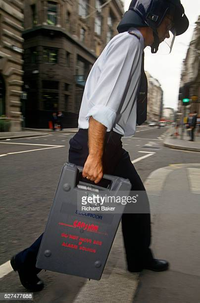 A Securicor guard delivers a cash box to a City of London bank Walking quickly to avoid delays in the street the employee of this security company...