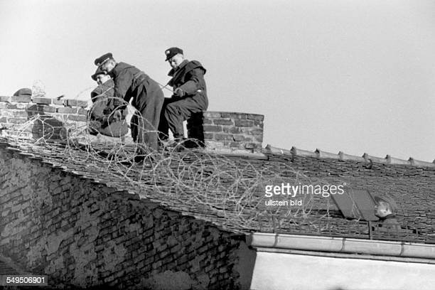 Securing the sector border at Bernauer Strasse with barbed wire on roofs