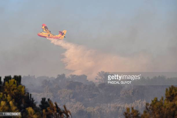 A Securite Civile Canadair firefighter plane drops water to fight a wildfire burning in the countryside near Generac southern France on August 2 2019...