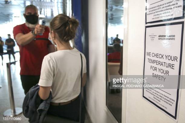A security agent checks the temperature of a woman using a 'no contact thermotere' arriving at the Napoleon Bonaparte airport in Ajaccio on July 14...