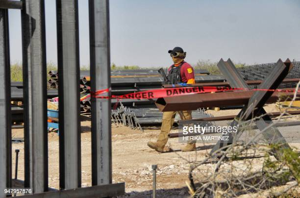 A security agent patrols the construction site of the border wall being built by order of US President Donald Trump on the border between Ciudad...