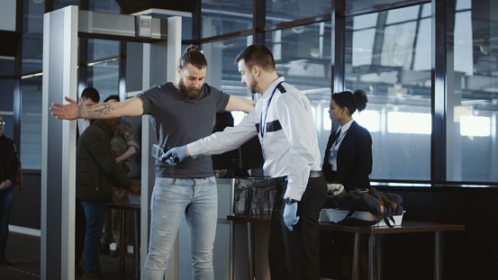 Security agent patting down a male passenger 932264132