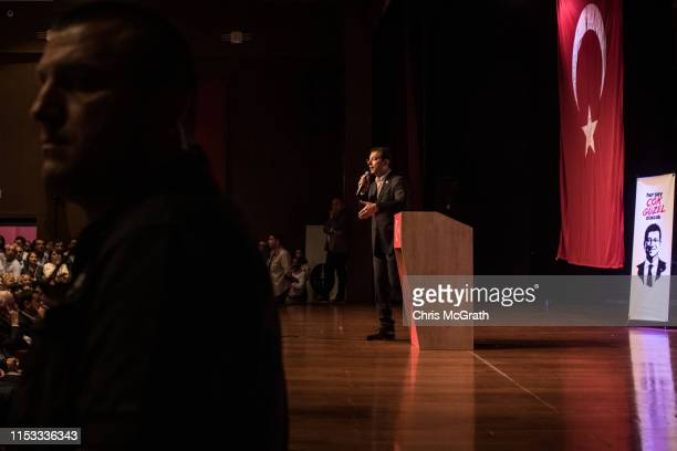 A security agent stands watch as Ekrem Imamoglu CHP Party candidate for mayor of Istanbul speaks to supporters at a cultural center during...