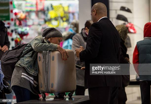 A security agent uses a metal detector to check a woman's suitcase as she enters a shopping center in Lille on November 21 as part of increased...