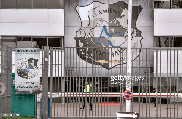 A security agent walks at the entrance of the Stade de la Licorne with the logo of French L1 football club Amiens SC in Amiens northern France on...