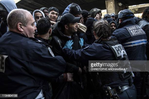 Security agents and police officers hold back migrants during the evacuation of a makeshift camp at Porte de la Chapelle in the north of Paris on...