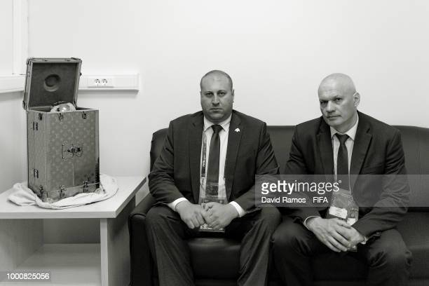 Security agents sits next to The World Cup trophy ahead of the 2018 FIFA World Cup Russia Final between France and Croatia at Luzhniki Stadium on...