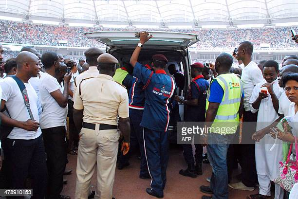 Security and health officials carry bodies into an ambulance after a stampede in Abuja National Stadium where thousands of jobseekers came to apply...